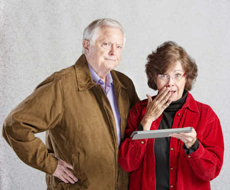 Suspicious man and embarrassed woman holding tablet photo