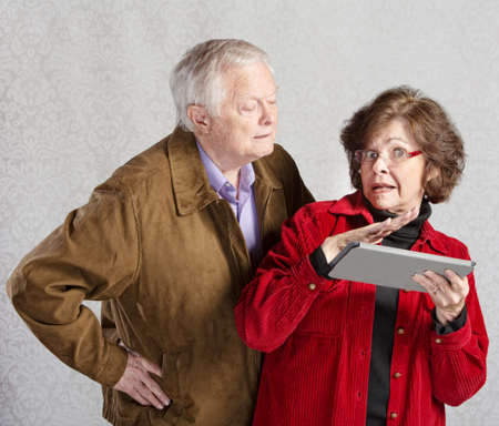 Suspicious man looking over shoulder of woman with tablet photo