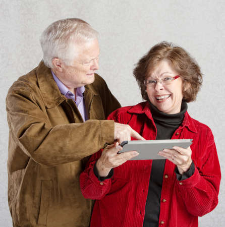 Confused man pointing at smiling womans tablet photo