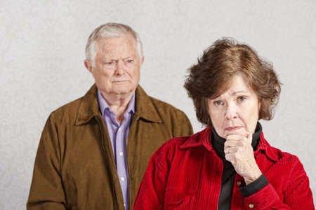Serious woman with hand on chin with man watching photo