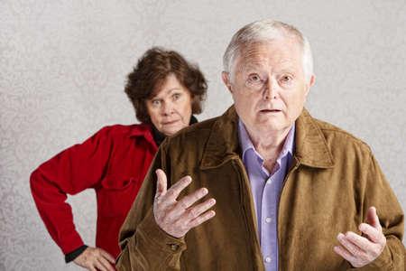 pareja discutiendo: Frustrado hombre mayor con las manos arriba y la mujer molesta