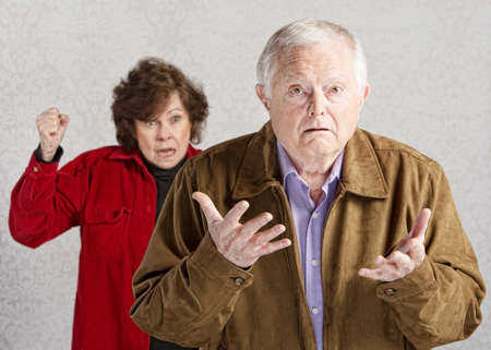 Confused elderly man with angry older woman