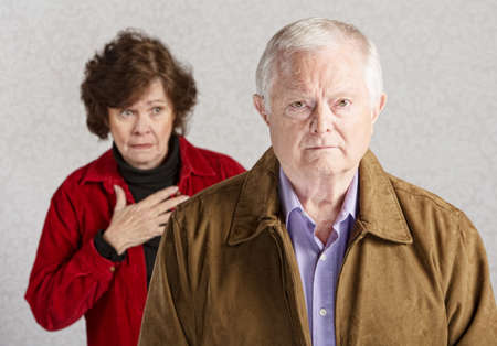 Concerned senior woman with hand on chest behind sad man photo