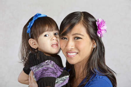 native american baby: Beautiful young Asian mother holding little girl