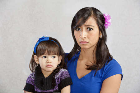 Disappointed Asian mother holding serious female toddler photo