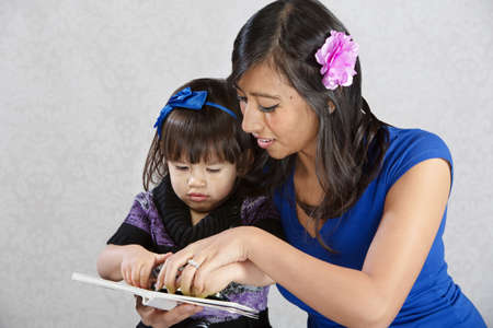native american baby: Pretty young Native American mother reading to toddler