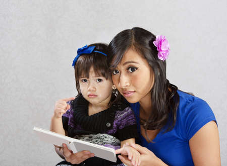 Cute child and young woman reading a story photo