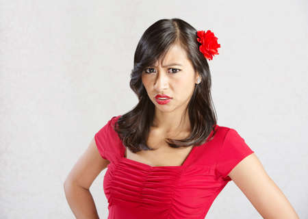 disgusted: Single disgusted Asian female in red dress