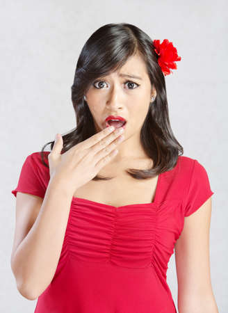 Shocked young Hispanic woman in red with flower in  hair Stock Photo