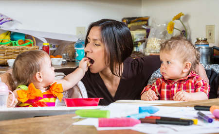 messy house: A Baby feeds her mother at breakfast Stock Photo