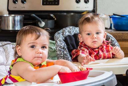 highchair: A baby reaches out to get his sisters cereal