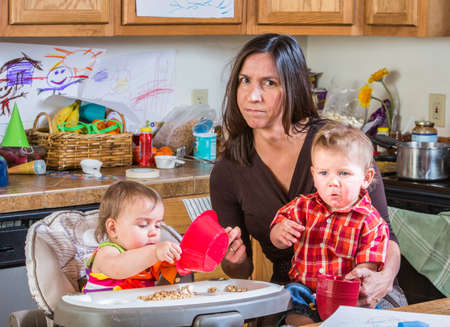 Stressed out mother in kitchen with her babies photo