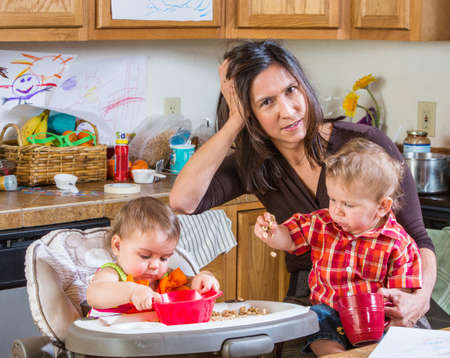 Stressed out mother in kitchen with her babies