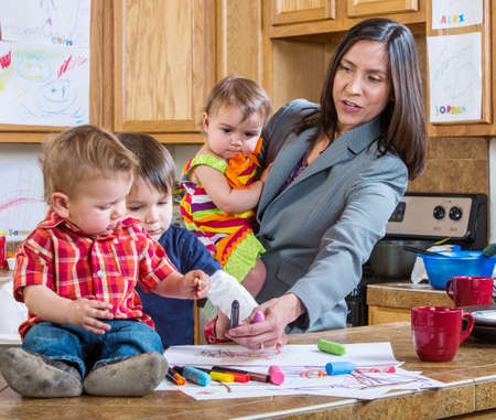 A mother in the kitchen plays with her chilrdren