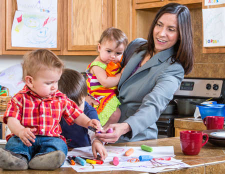 A mother in the kitchen plays with her babies