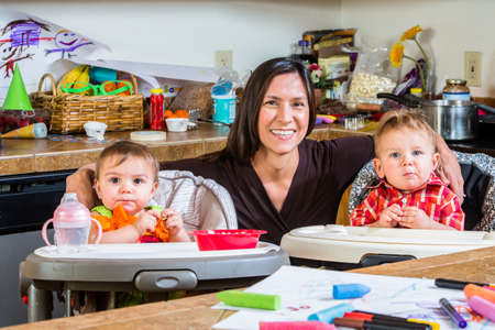 messy house: Smiling mother poses with her babies