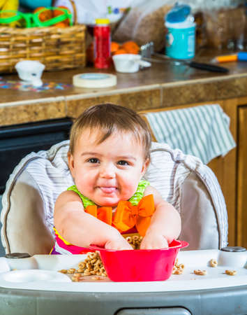 messy house: Baby girl eats breakfast in her highchair