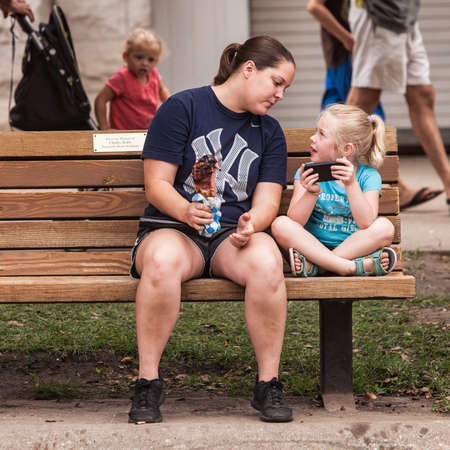 attendee: DES MOINES, IA USA - AUGUST 10: Attendees at the Iowa State Fair. Unidentified girls look at smart phone at Iowa State Fair on August 10, 2014 in Des Moines, Iowa, USA. Editorial