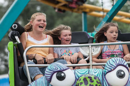 DES MOINES, IA USA - AUGUST 10: Unidentified girls enjoy a carnival thrill ride at the Iowa State Fair on August 10, 2014 in Des Moines, Iowa, USA.