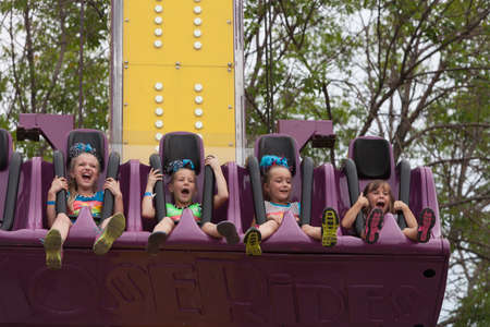 attendee: DES MOINES, IA USA - AUGUST 10: Unidentified girls enjoy a carnival thrill ride at the Iowa State Fair on August 10, 2014 in Des Moines, Iowa, USA.