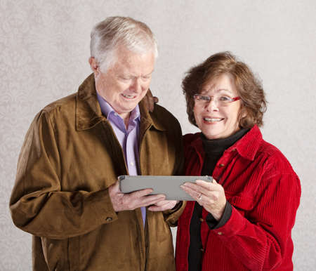Happy older man and woman holding a tablet computer photo
