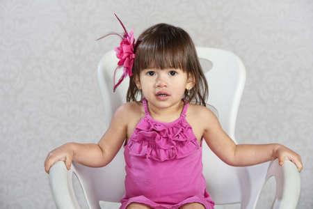 niños latinos: Niño lindo en silla con cinta de color rosa en el pelo