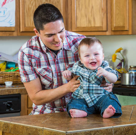 mess: Father plays with laughing baby in kitchen Stock Photo