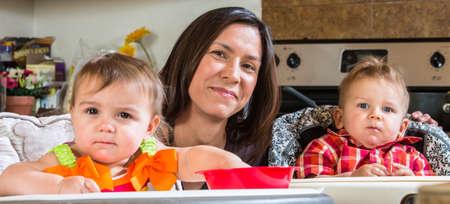 trabajando en casa: Una madre en la cocina, posa con los beb�s Foto de archivo