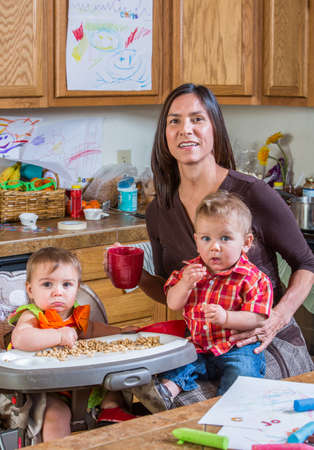 messy kitchen: A mother in the kitchen poses with babies