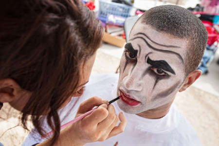 comedic: Makeup artist lining lips of male circus clown