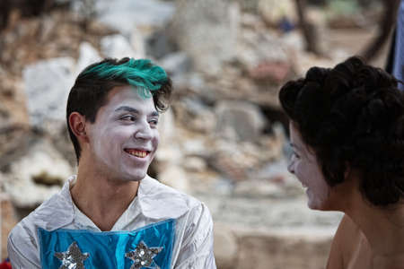 bizarre: Clown with green hair laughing backstage with partner