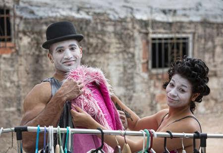 cirque: Cute cirque clowns fitting pink coat outdoors Stock Photo