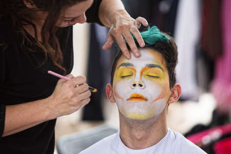 circus performers: Young male clown getting makeup on face Stock Photo