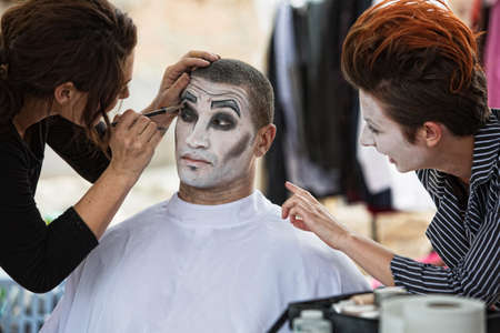 make up artist: Group of clowns backstage with make up artist Stock Photo