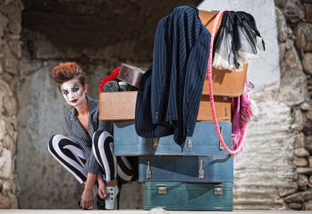 heap of role: Grinning female clown squatting near stack of suitcases Stock Photo
