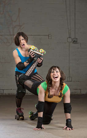 harassing: Bully roller derby skater twisting the leg of a woman