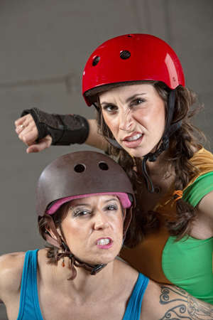 tough: Two tough female roller derby skaters with clenched teeth Stock Photo