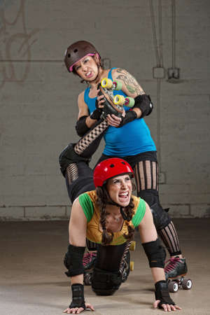 harassing: Hostile roller derby skater attacking woman with leg twist