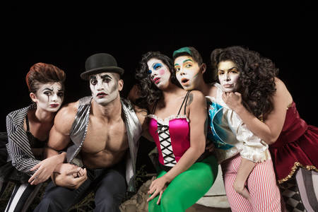 Five serious cirque clowns on theater stage