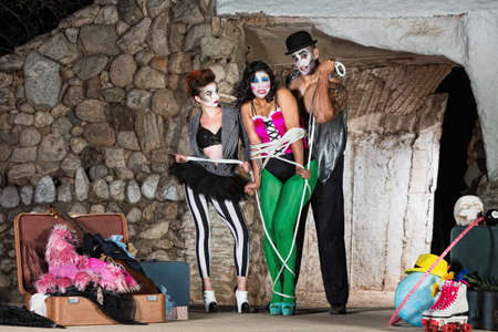 damsel: Group of cirque clowns tying up woman with rope Stock Photo