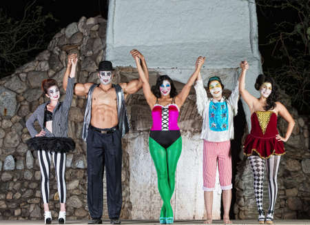 stage actors: Group of happy cirque clowns holding hands Stock Photo
