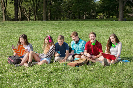 Laughing group of male and female students outdoors Stock fotó