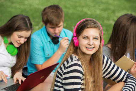 cute teen girl: Smiling cute teen girl with braces and pink headphones
