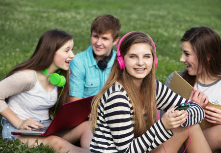 Cute teen with friends sitting outdoors on lawn