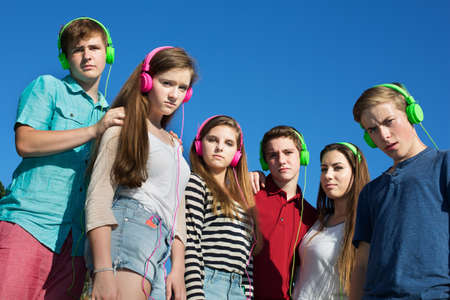 Group of offended teens in pink and green headphones