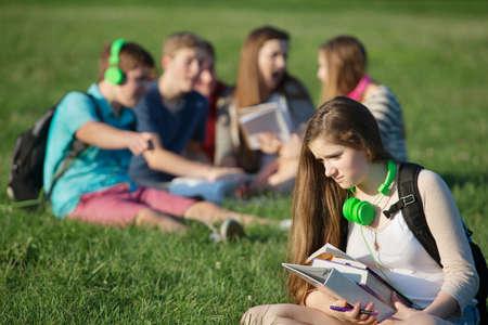 adolescencia: Adolescente femenino triste que se sienta al aire libre con los libros