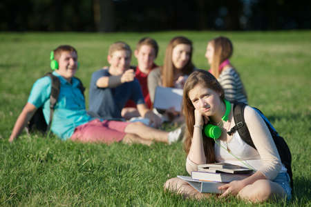 Pouting teen girl near group on grass outdoors