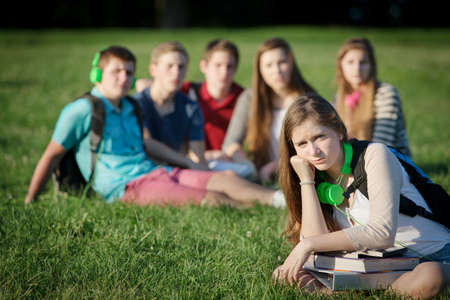 outcast: Lonely female teen student sitting near group