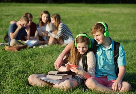 pareja de adolescentes: Estudiantes adolescentes sentados y escuchando reproductor de mp3 juntos Foto de archivo