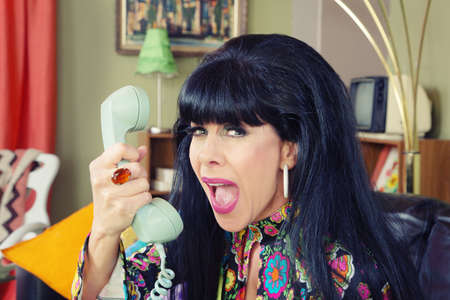60s adult: Woman yelling into phone with bad connection